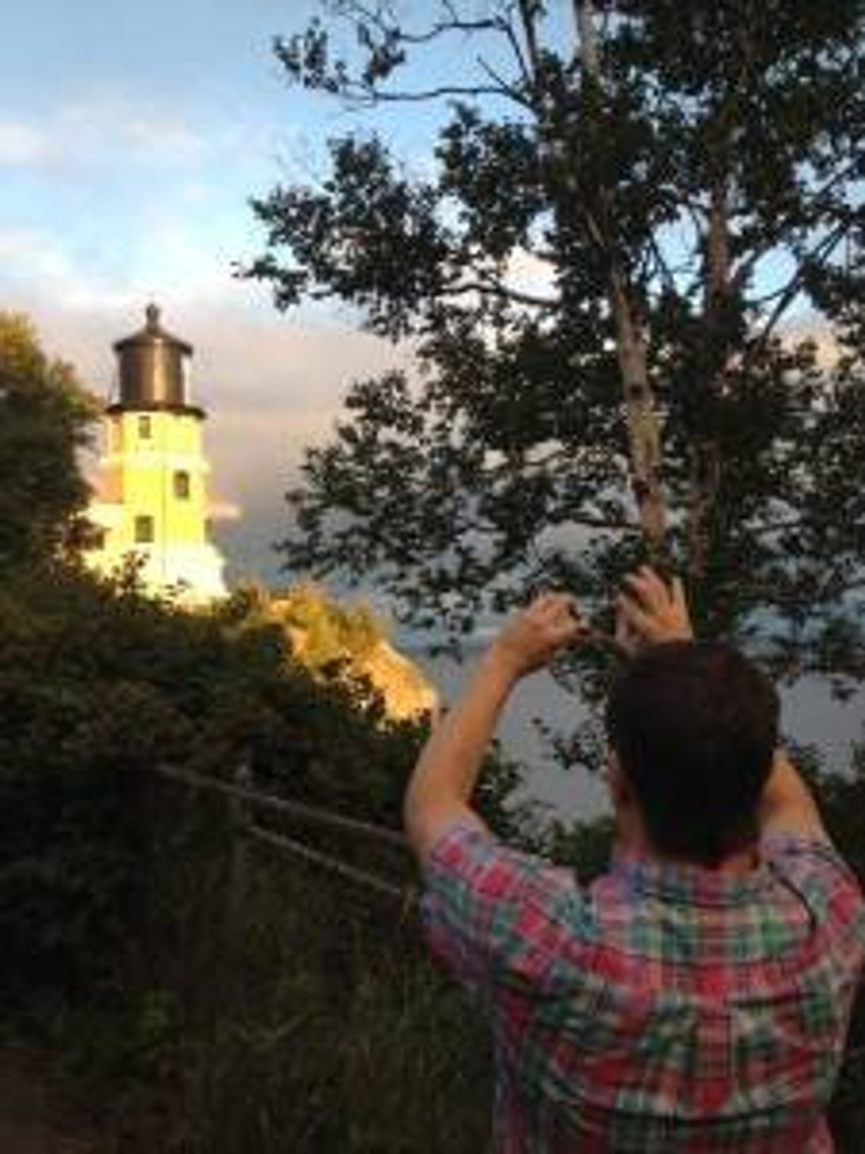 image of a man taking a picture of a lighthouse