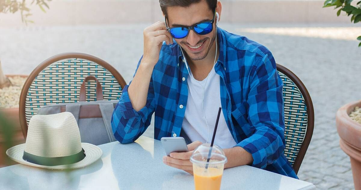 Closeup photo of young Caucasian male looking at display of his cellphone while listening to mate or audio content in web as he is spending leisure time in outdoor cafe. Rewire PBS Our Future Privacy
