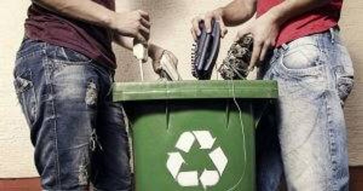 Two people putting broken electronics into a recycling bin pbs rewire