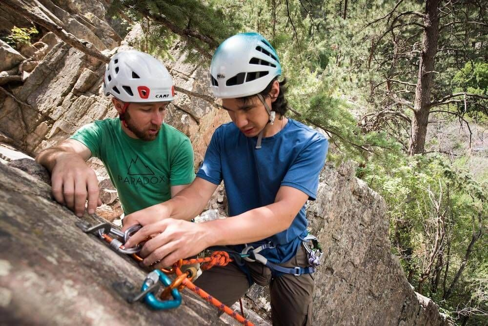 A climbing instructor assists a man who is blind on a climb. Rewire PBS