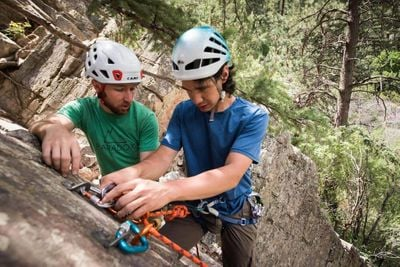 Two people with helmets fix climbing gear while in the forest.