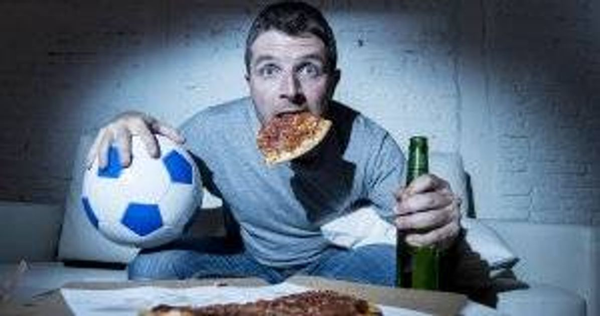 Male football fan watching soccer game on TV at home with soccer ball and pizza in his mouth. Stress-Eating pbs rewire