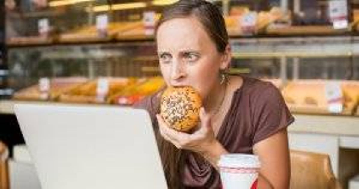 Young woman working at the computer and eating bread. Stress-Eating pbs rewire