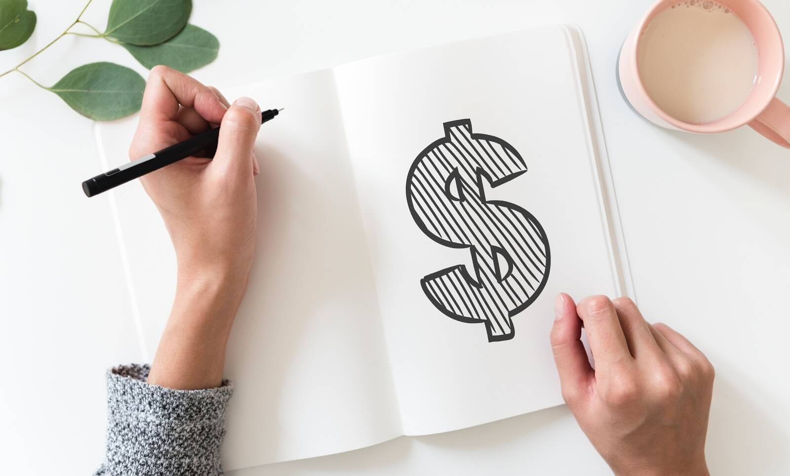 A woman's hands as seen from above, holding a pen above a journal with a large dollar sign written on it. Rewire PBS Work Freelance or Contract