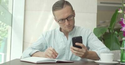 Man checking his phone and taking financial notes. Personal Finance pbs rewire