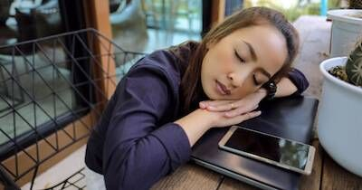 Young woman sleeping on top of her laptop at her desk. Work Addiction pbs rewire