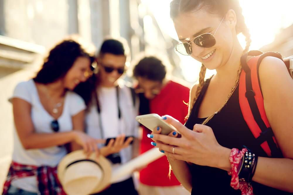 Young tourists searching for location both on mobile phone and map. Rewire PBS Our Future Get Offline