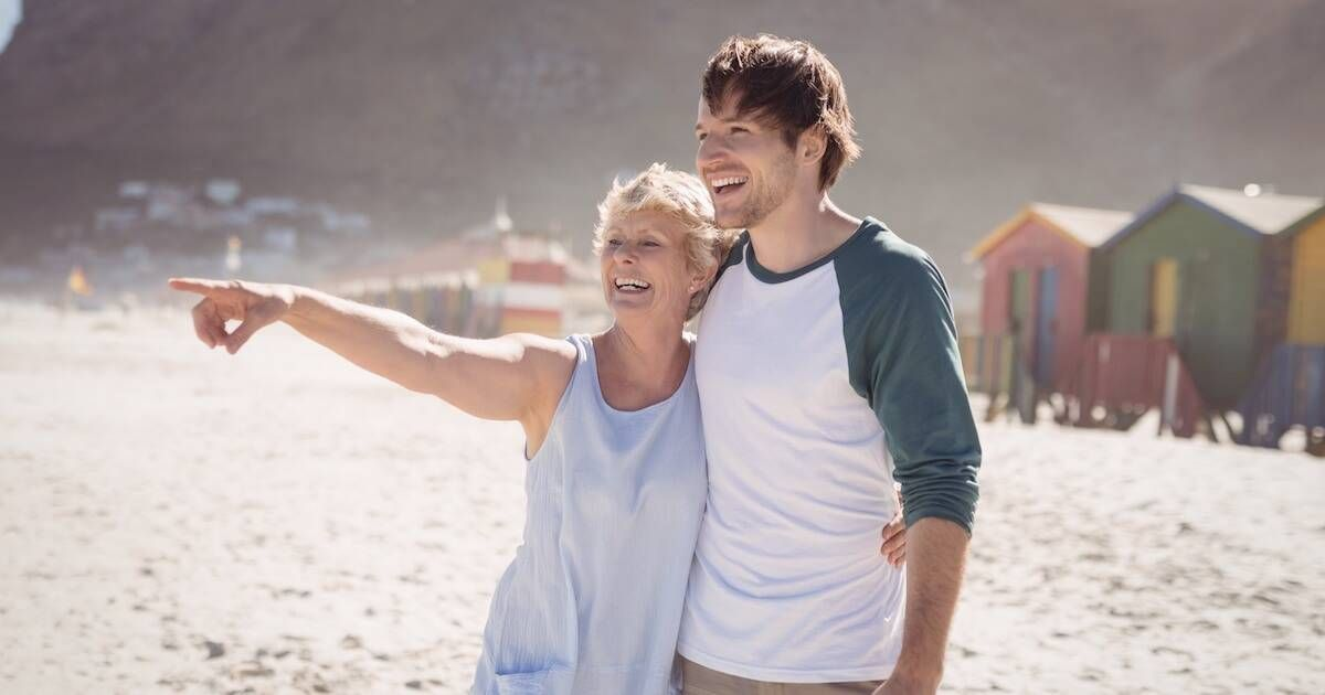 Older mother pointing something out to her adult son on the beach. Understand Your Mom pbs rewire