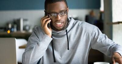 Younger African-American man on his cell phone in front of his laptop computer. Remote Work pbs rewire