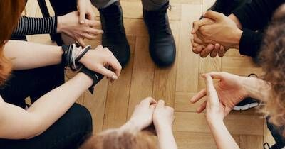 A group sits in a circle, as seen from above. Only their hands and feet are visible. Rewire PBS Love Mental Health Ally