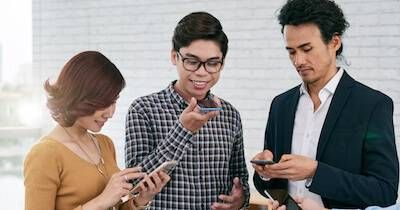 Three coworkers using their smartphone's voice search abilities. Tech Industry pbs rewire