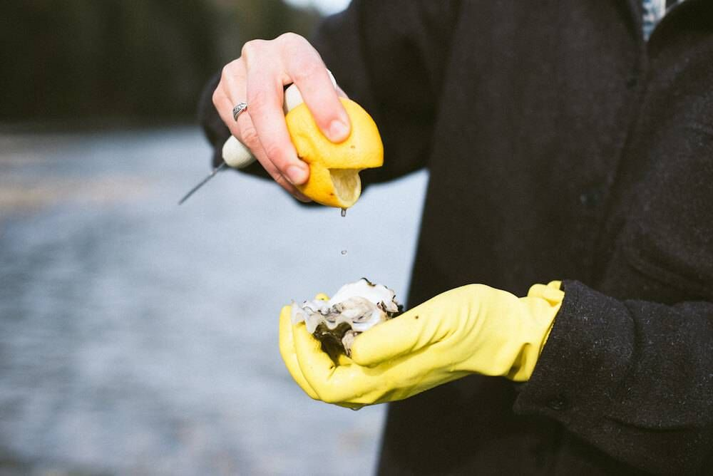 Photo of hands squeezing a lemon on to a fresh oyster. Rewire PBS Living Oysters