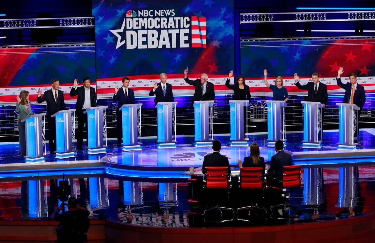 Democratic presidential candidates, author Marianne Williamson, former Colorado Gov. John Hickenlooper, entrepreneur Andrew Yang, South Bend Mayor Pete Buttigieg, former Vice President Joe Biden, Sen. Bernie Sanders, I-Vt., Sen. Kamala Harris, D-Calif., Sen. Kirsten Gillibrand, D-N.Y., former Colorado Sen. Michael Bennet, and Rep. Eric Swalwell, D-Calif., raise their hands when asked if they would provide healthcare for undocumented immigrants, during the Democratic primary debate hosted by NBC News at the Adrienne Arsht Center for the Performing Arts, Thursday, June 27, 2019, in Miami. Rewire PBS Our Future Democratic Debates