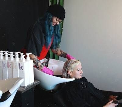 Photo of a hairstylist with blue hair, washing a client's hair in a salon. Rewire Work PBS Trade School