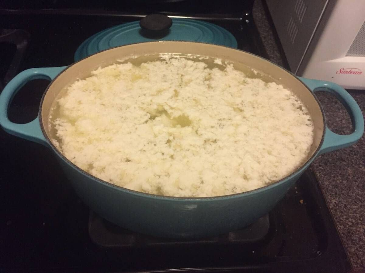 Photo of a large pot with curdled cream-colored liquid. Rewire Living PBS Mozzarella