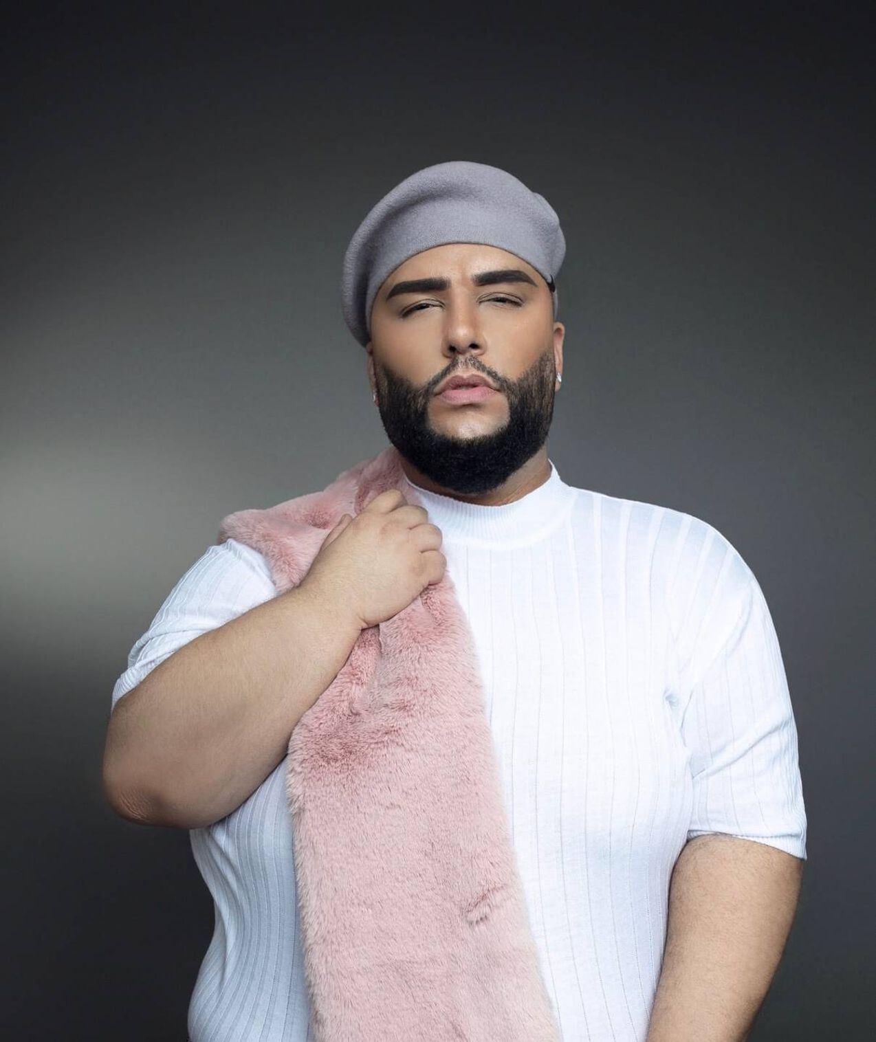 Fashion photograph of a man in a grey beret and a white shirt with a pink faux-fur scarf. Rewire PBS Living Ady Del Valle