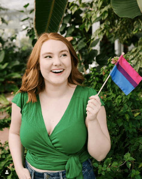 Photo of Eva Bloom smiling with a flag. Rewire PBS Our Future Sexual Health