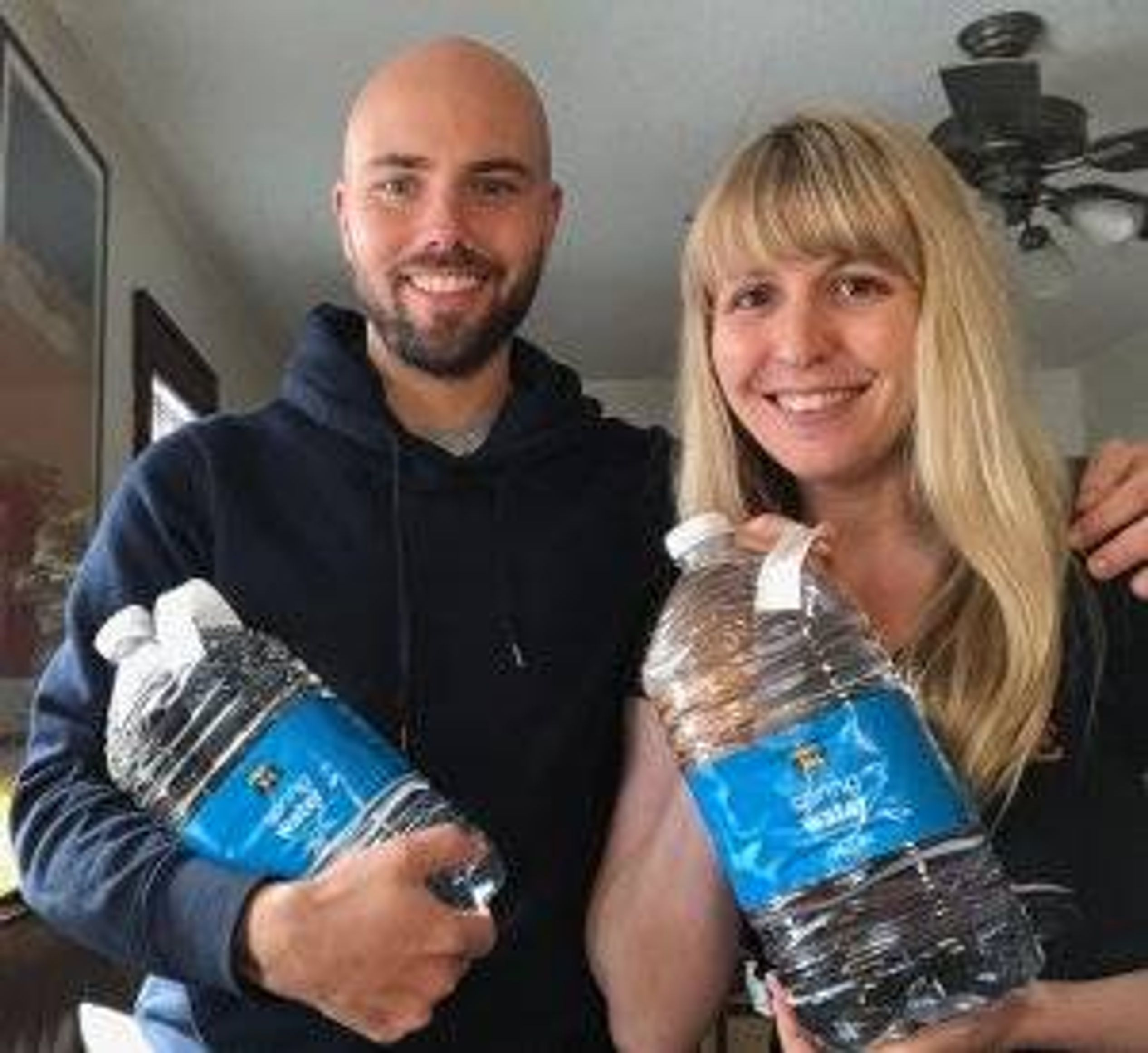 A smiling couple pose with two large bottles of water. Rewire PBS Love Coronavirus