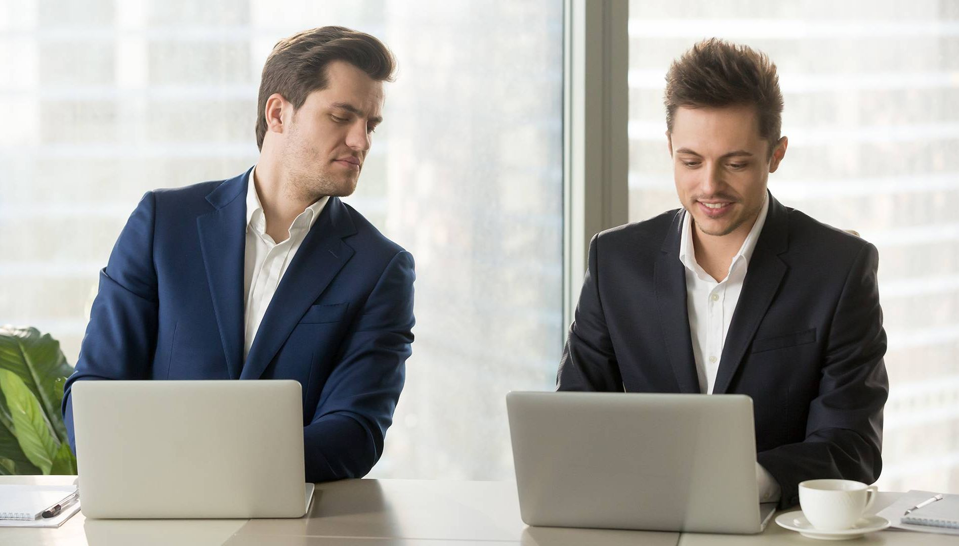 Curious businessman secretly looking at laptop screen of colleague. Rewire PBS Work Copycat