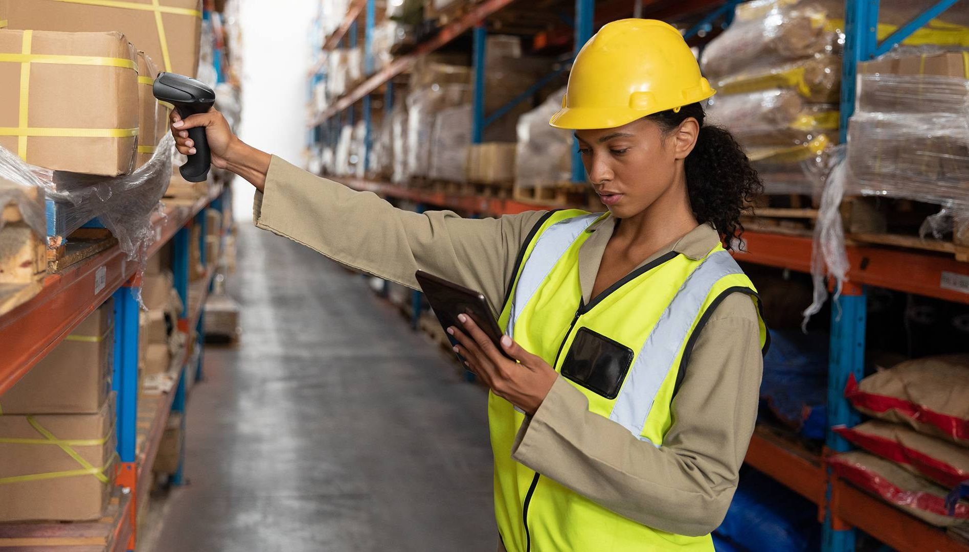 Female worker scanning package with barcode scanner while using digital tablet in warehouse. Rewire PBS Our Future Rights at Work