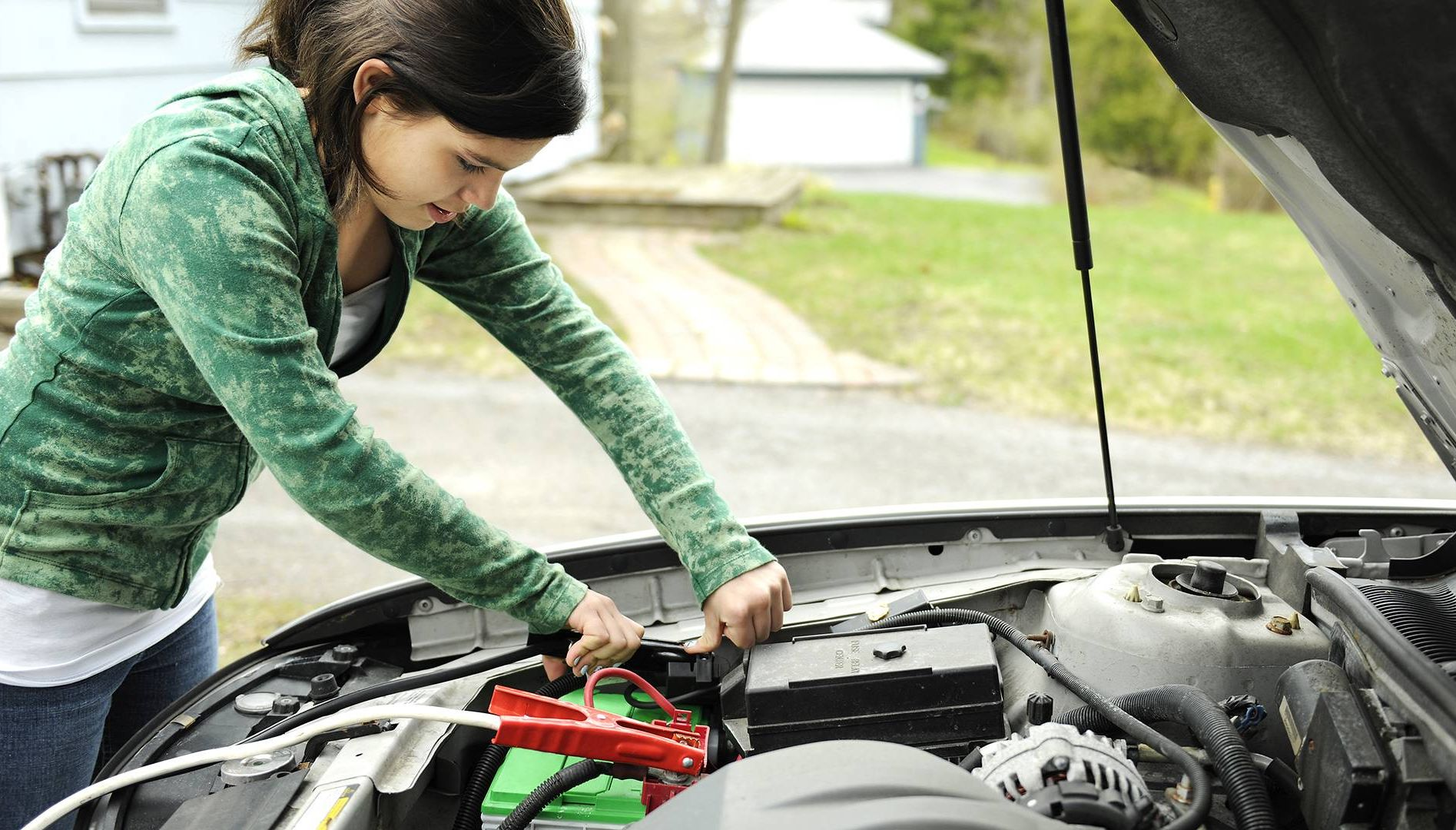 Photo of a young woman jump starting a car. Rewire PBS Living Car Care