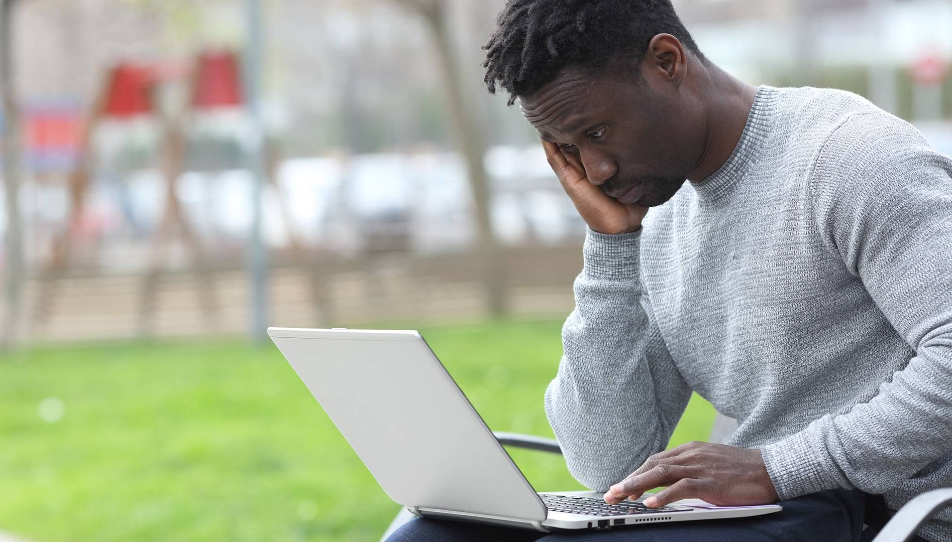 Photo of a worried black man reading bad news on laptop at the park. Rewire PBS Health Vicarious Trauma