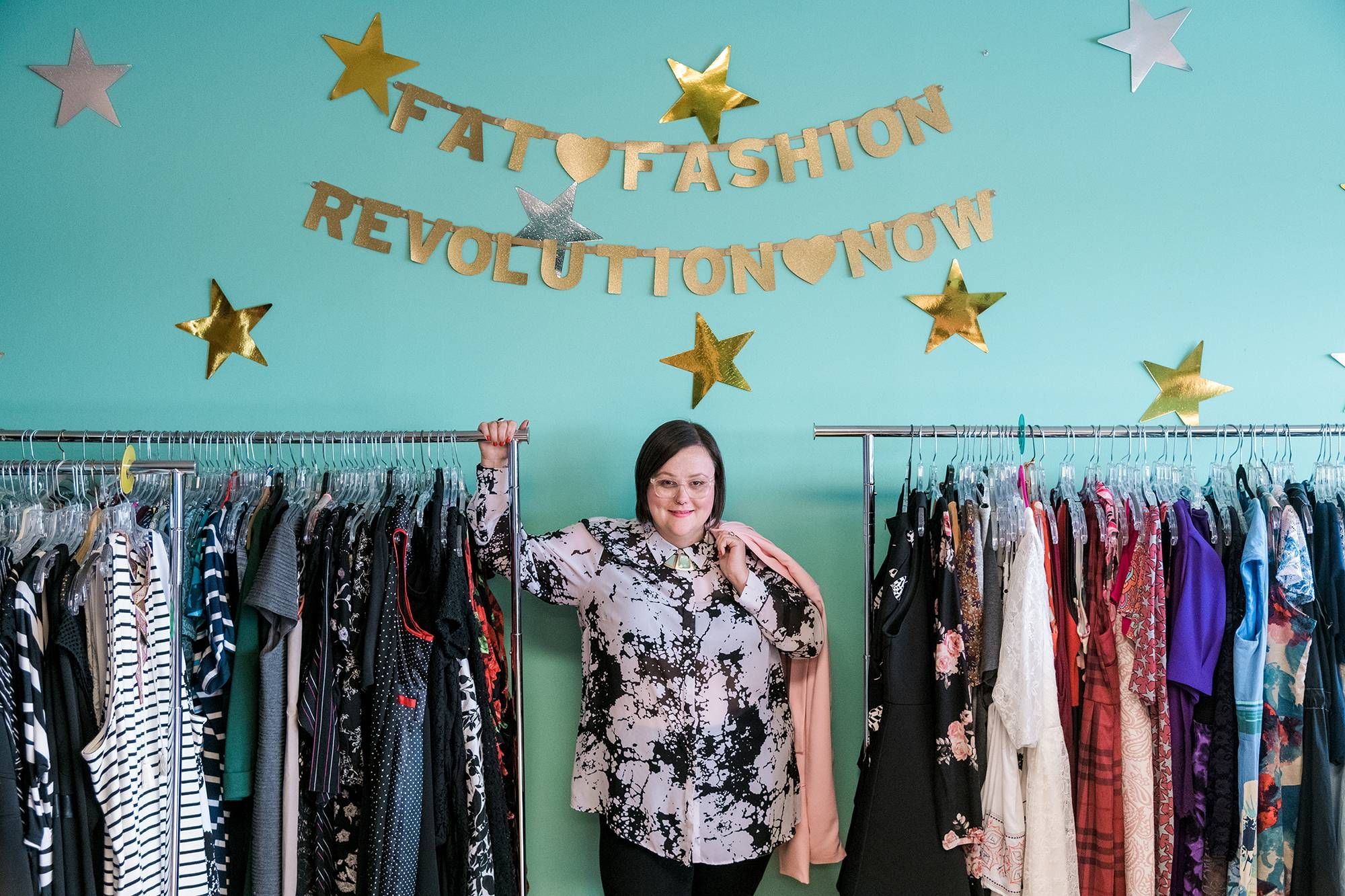 """Beethoven """"Bee"""" Thornton poses with a rack of clothes. Rewire PBS Living Plus Size Resale"""