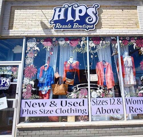 Exterior photo of the HIPS Resale Boutique front windows, full of clothes. Rewire PBS Plus Size Resale