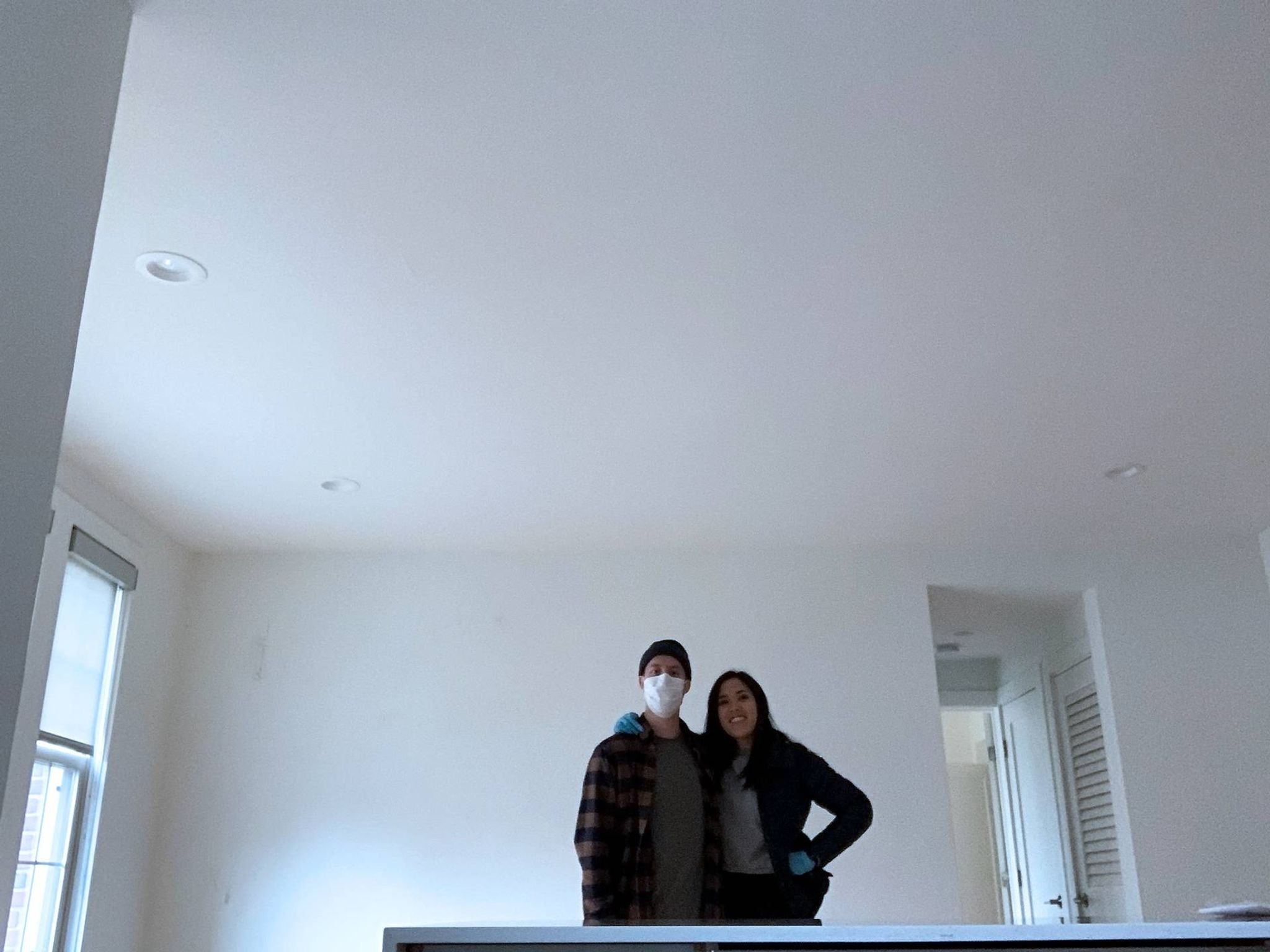 Photo of a couple, one wearing a face mask, in an empty apartment. Rewire PBS Living Moved