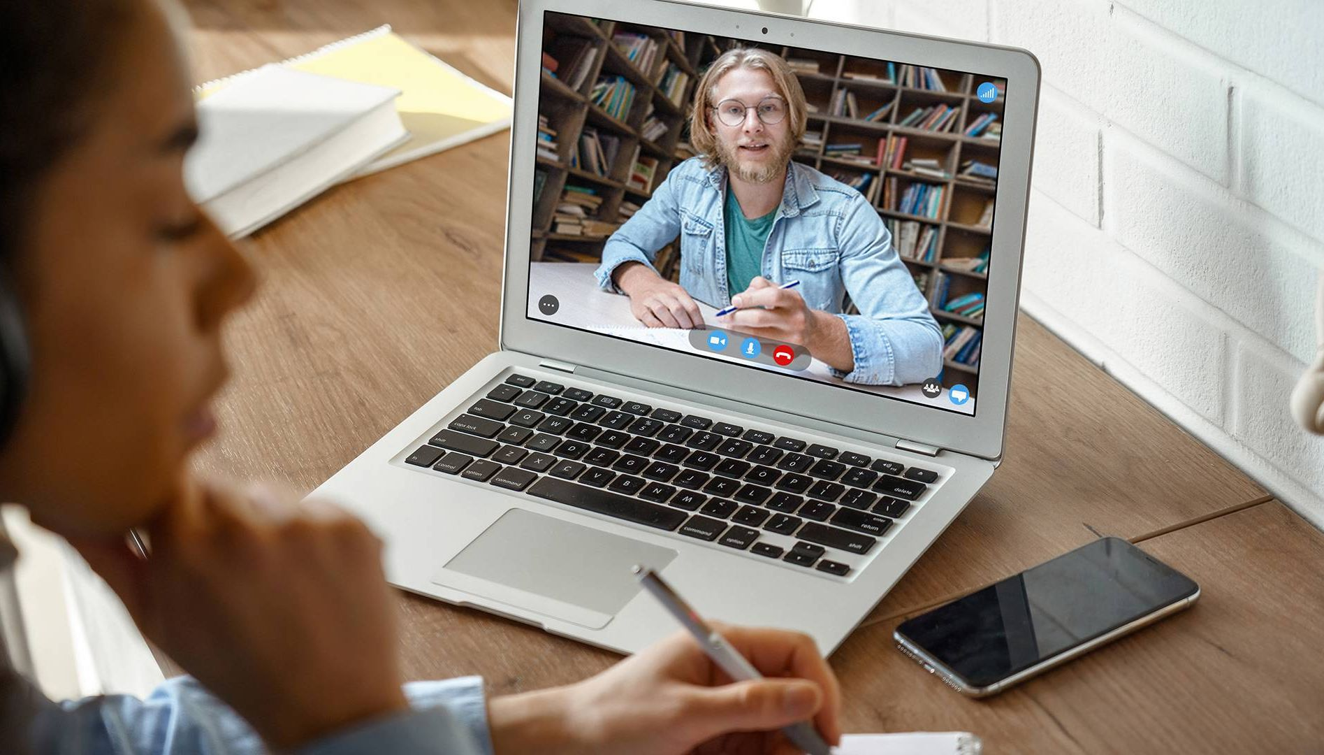 A young woman listens to a professor on video chat. Rewire PBS Our Future Online Schooling