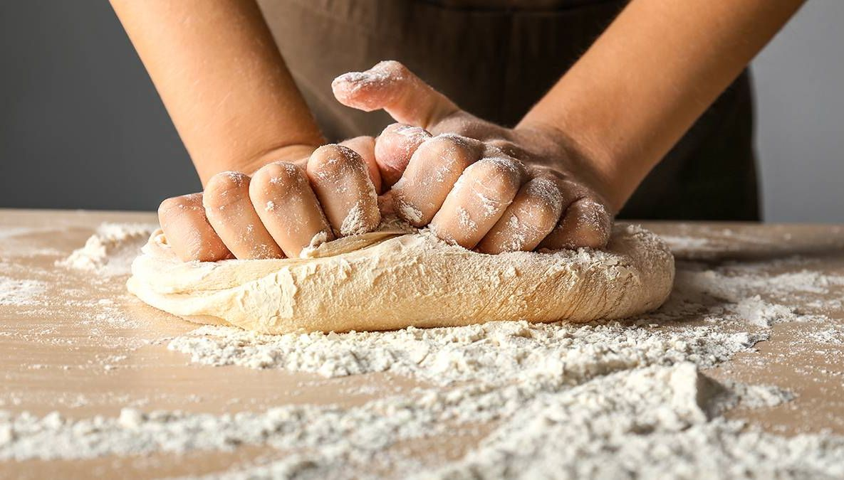 Person kneads dough with hands baking bread. REWIRE PBS Health Living analog hobbies