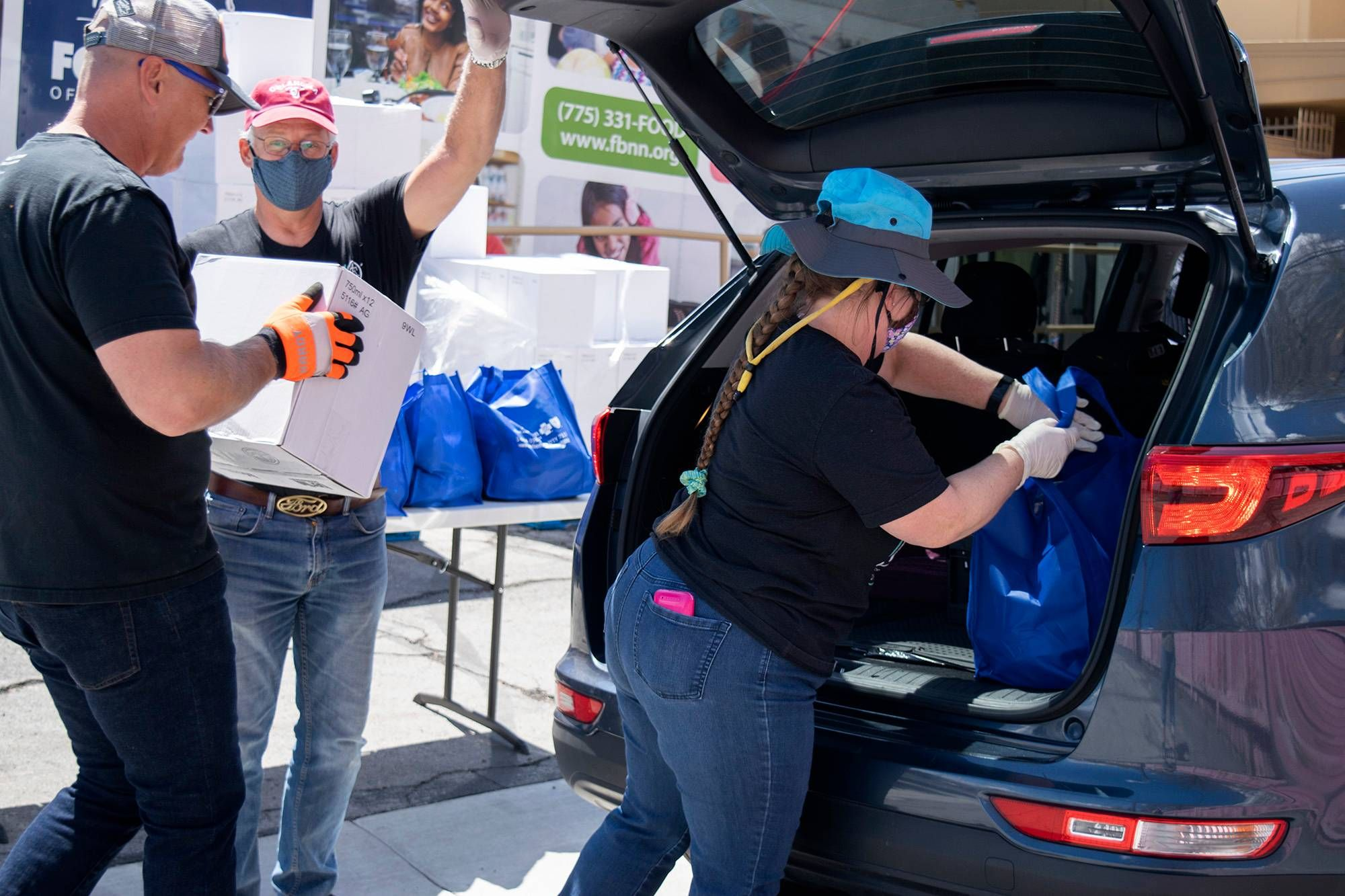 Volunteers load boxes and totes into the back of a car at a food bank distribution center. Rewire PBS Our Future