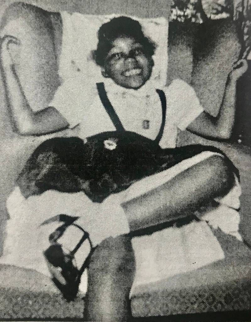 Black and white photo of a young girl, smiling at the camera. Rewire PBS Our Future Juneteenth