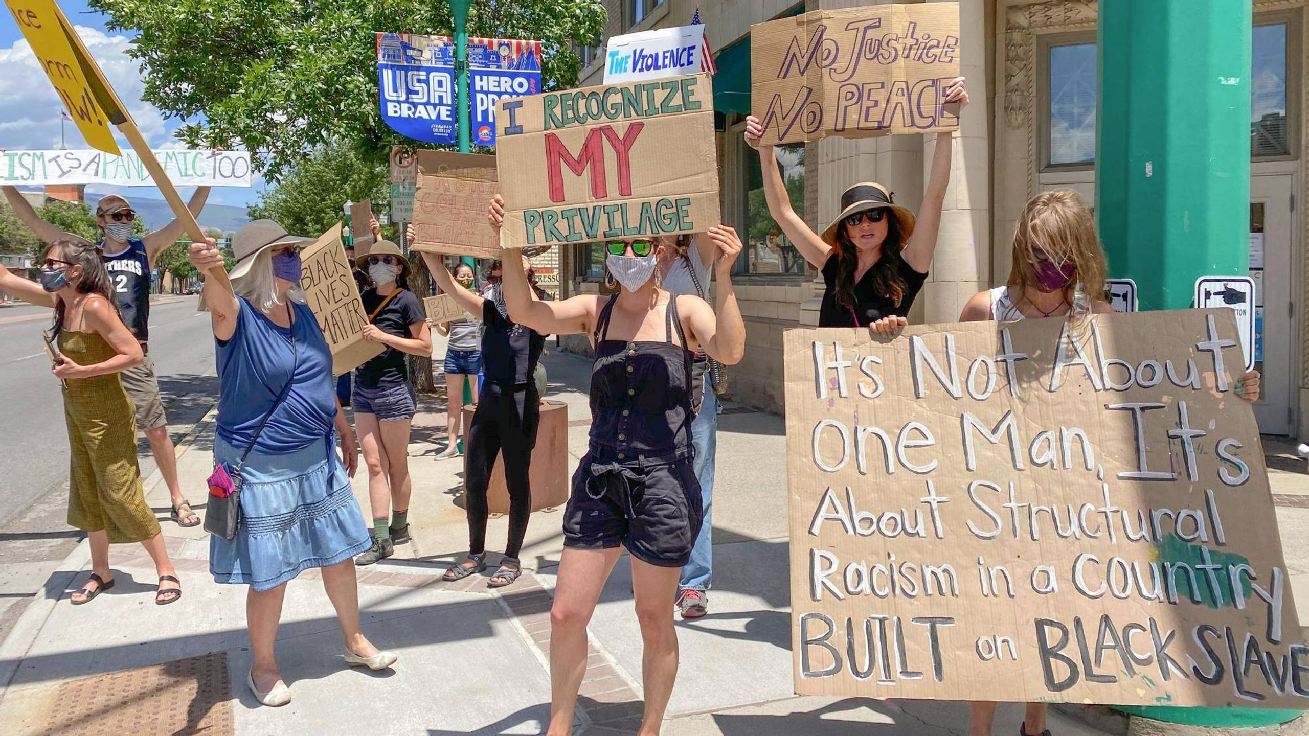 Protesters hold signs on a street corner in rural Colorado. Rewire PBS Our Future Activism Rural
