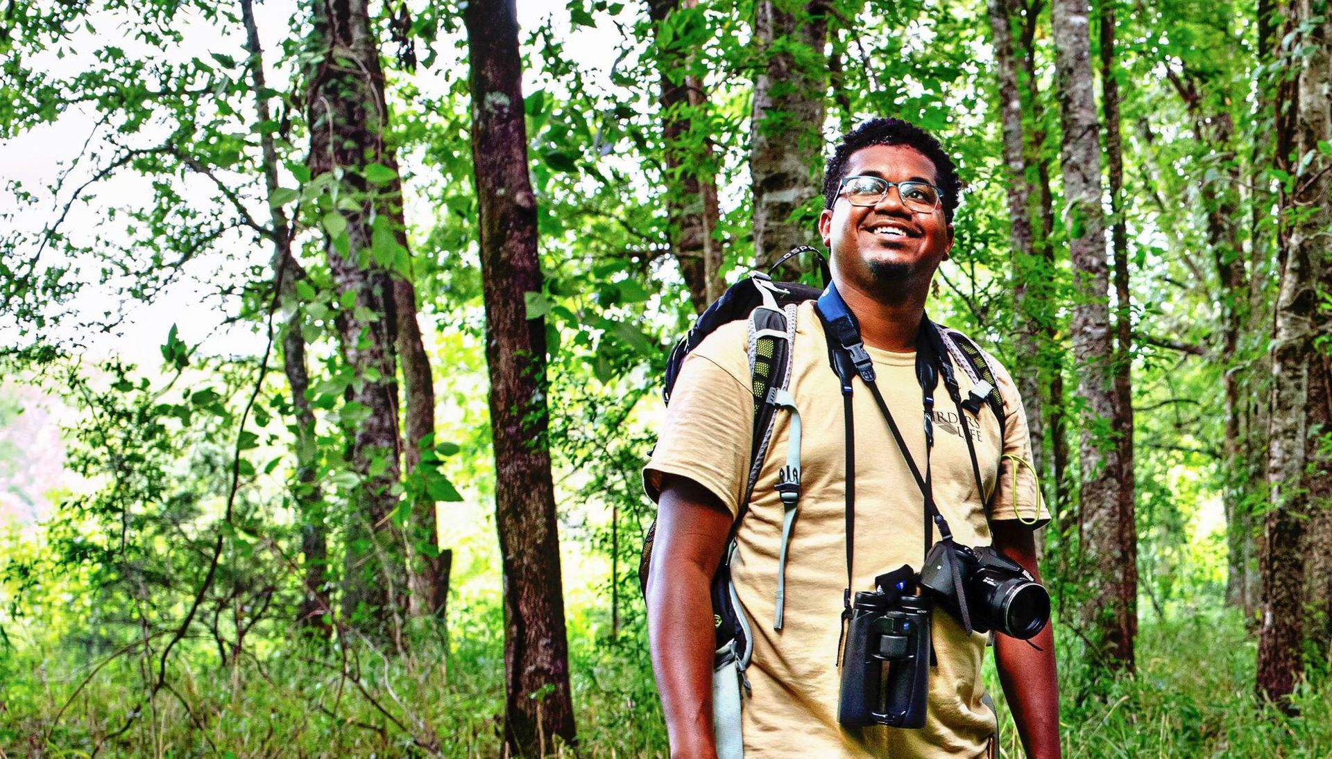 A birdwatcher stands in the woods and smiles. Rewire Our Future PBS Birding