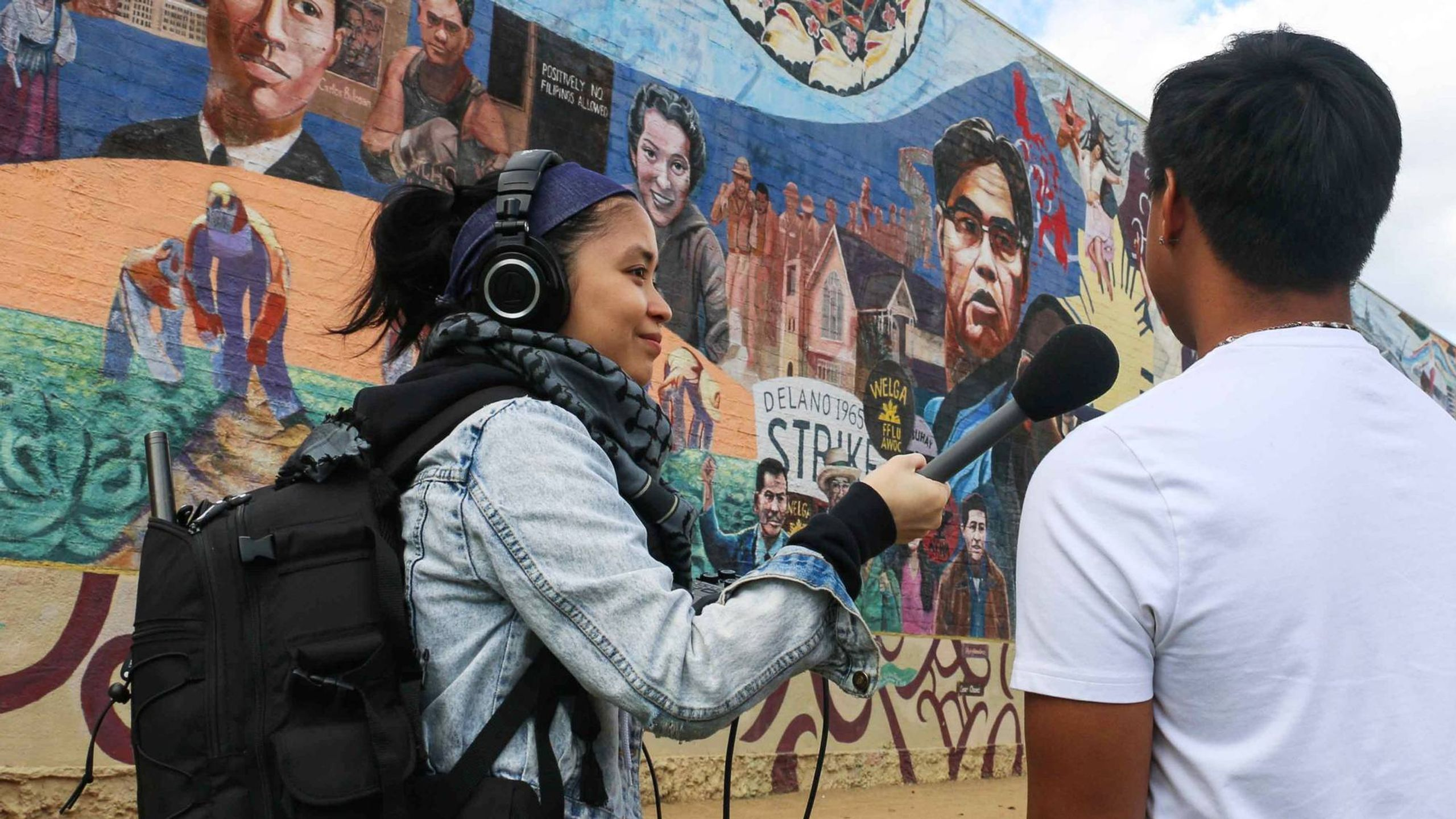 A young woman interviews a person in front of a mural. Rewire PBS Our Future Long Distance