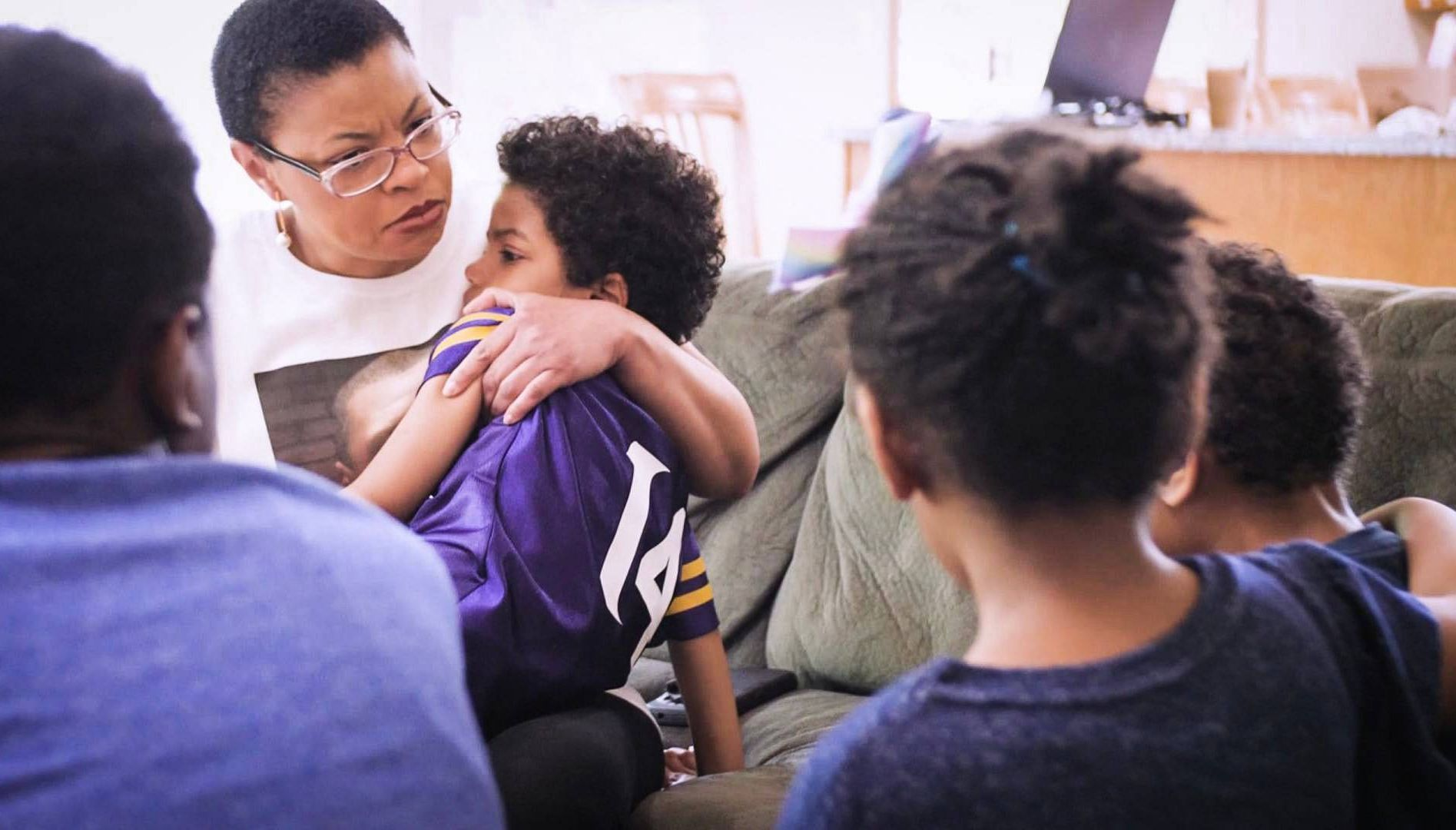 Photo of a Black woman hugging a child while 3 others look on. Rewire PBS Our Future Racism children