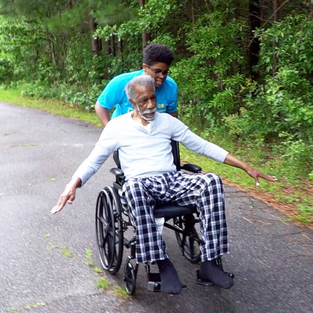 A young Black man pushes his grandfather in a wheelchair. Rewire PBS Love Caregiver Lumiere Rostick