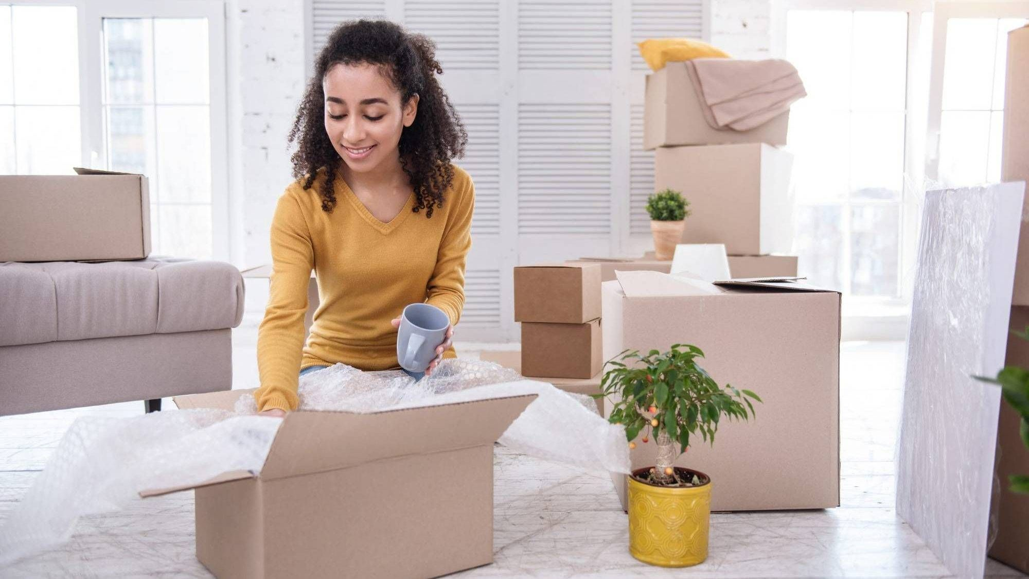 Young woman packing tea cup into box REWIRE PBS Living Alone Living