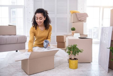 Young woman packing tea cup into box