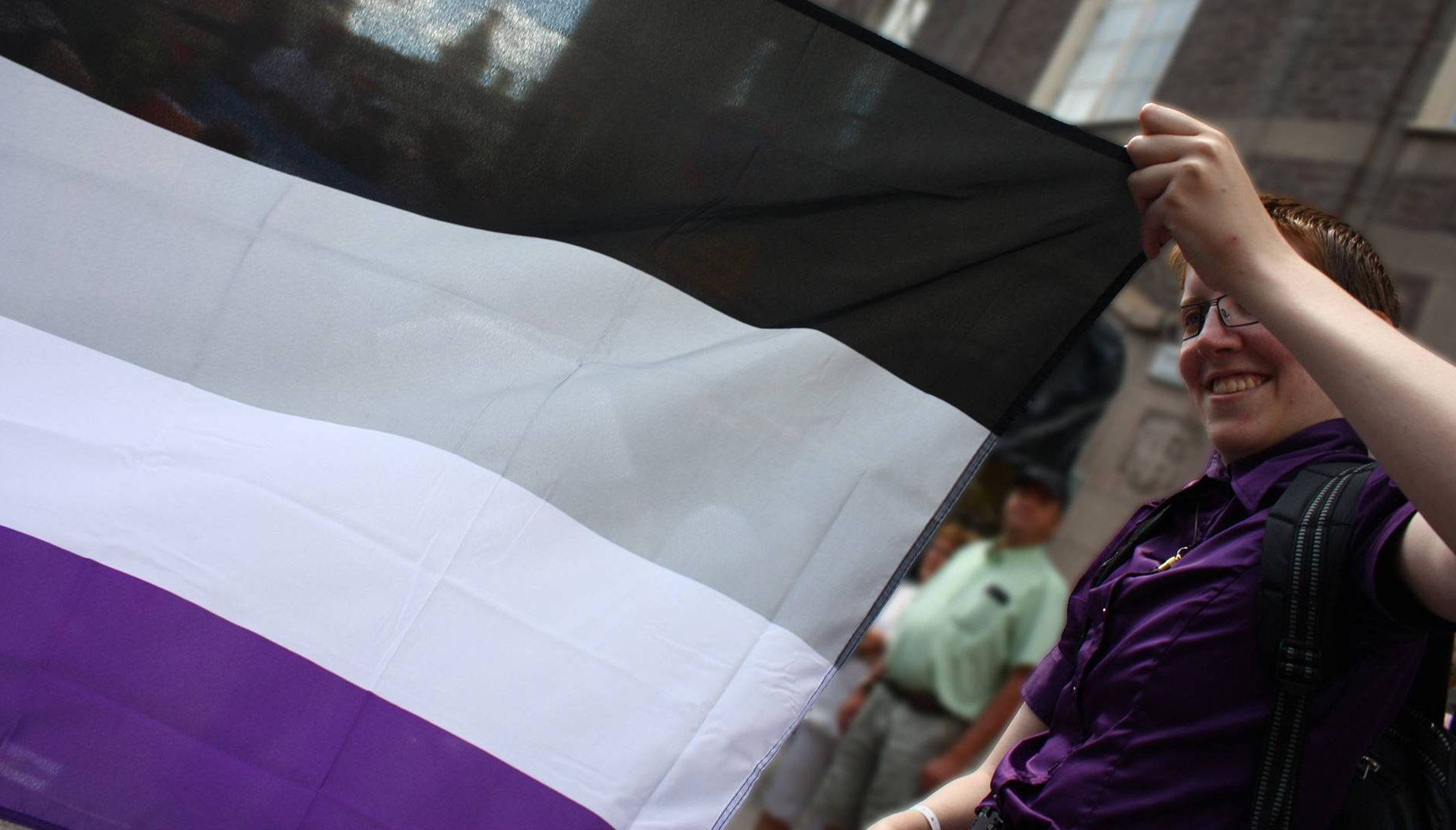 A person holds the edge of an asexual pride flag. Rewire PBS Love Asexual
