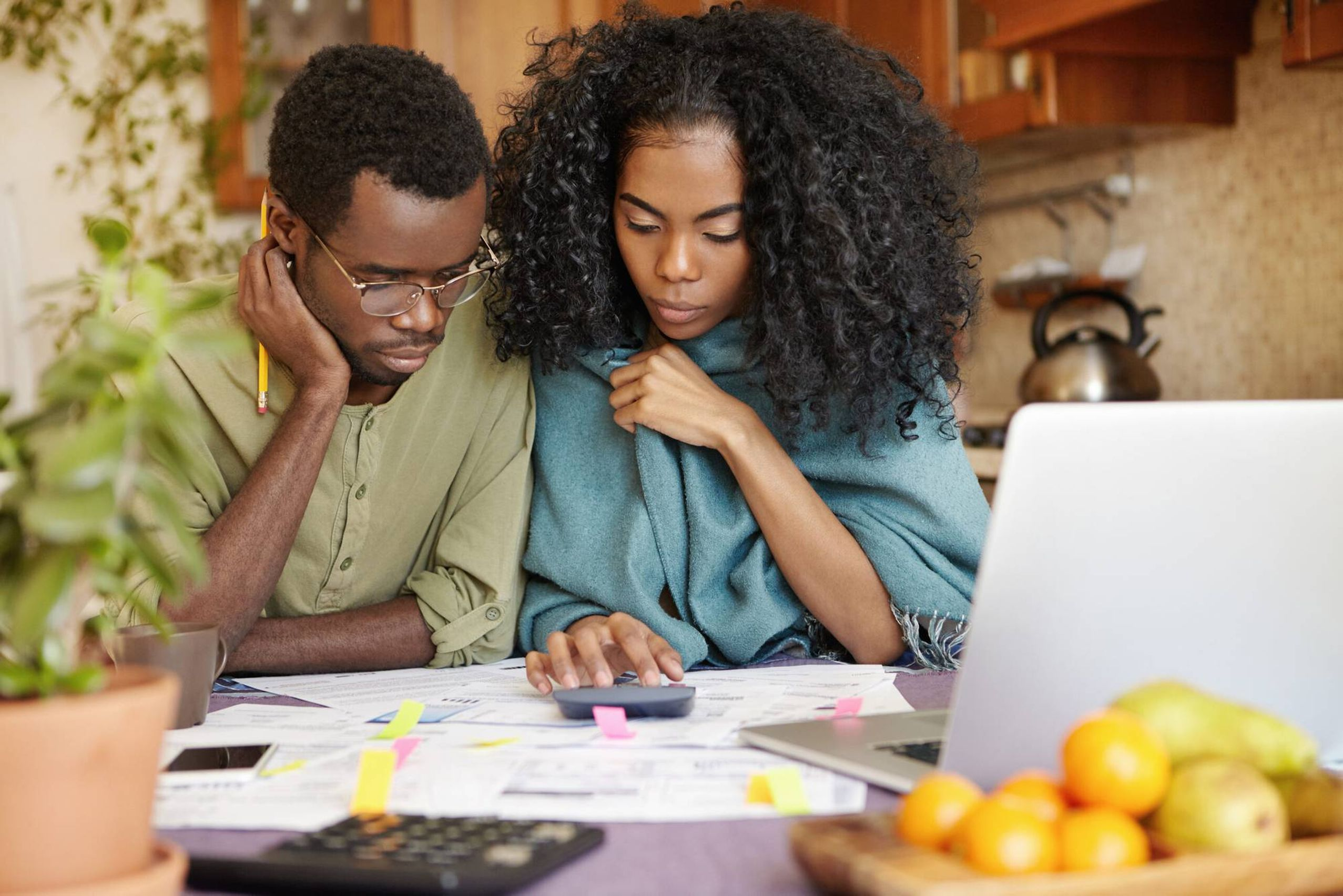 Young couple calculating their budget at the kitchen table. Rewire PBS Money Myths