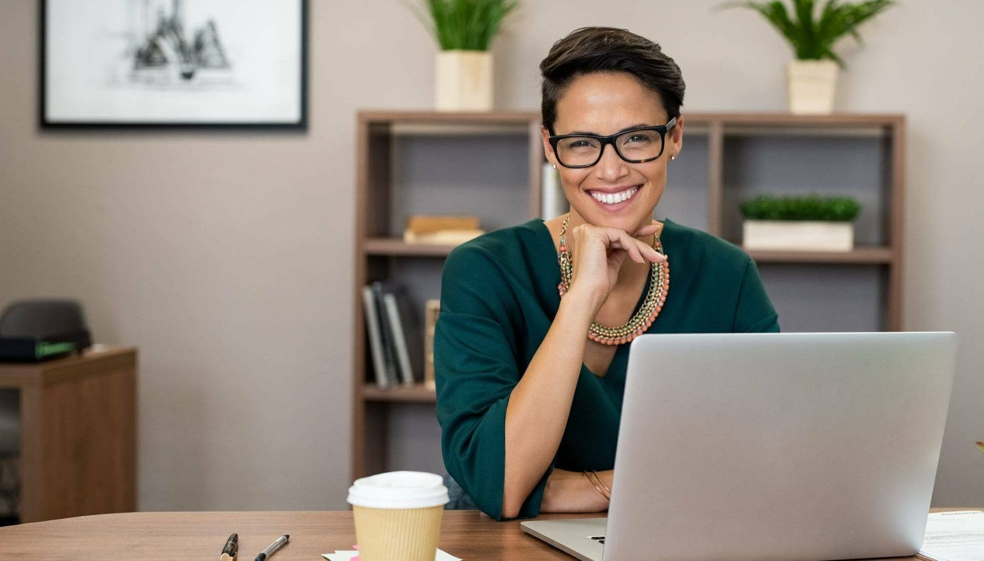 Woman sitting at laptop and smiling. Rewire PBS Work Introverts