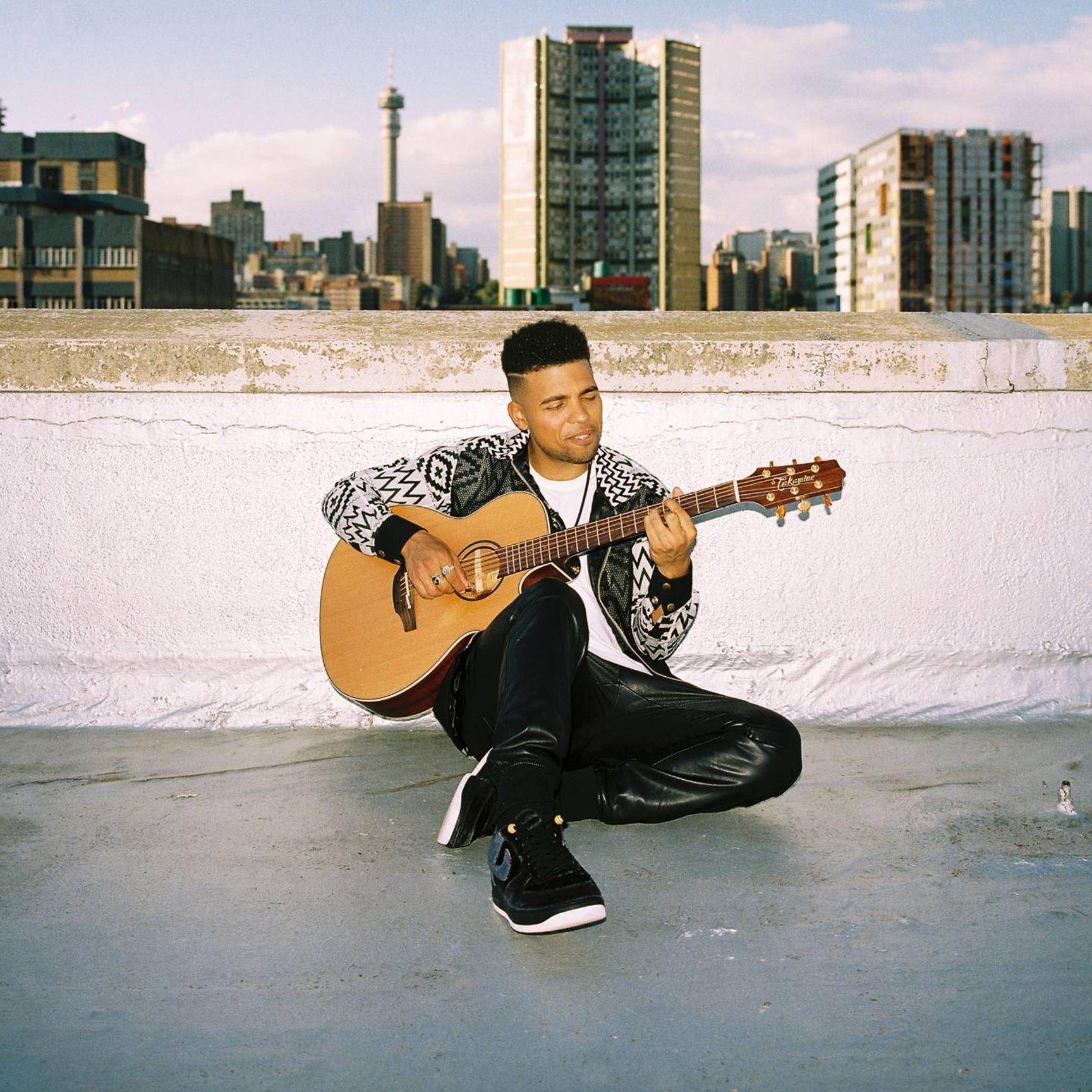 Devon Gilfillian plays guitar on a rooftop. Rewire PBS Our Future