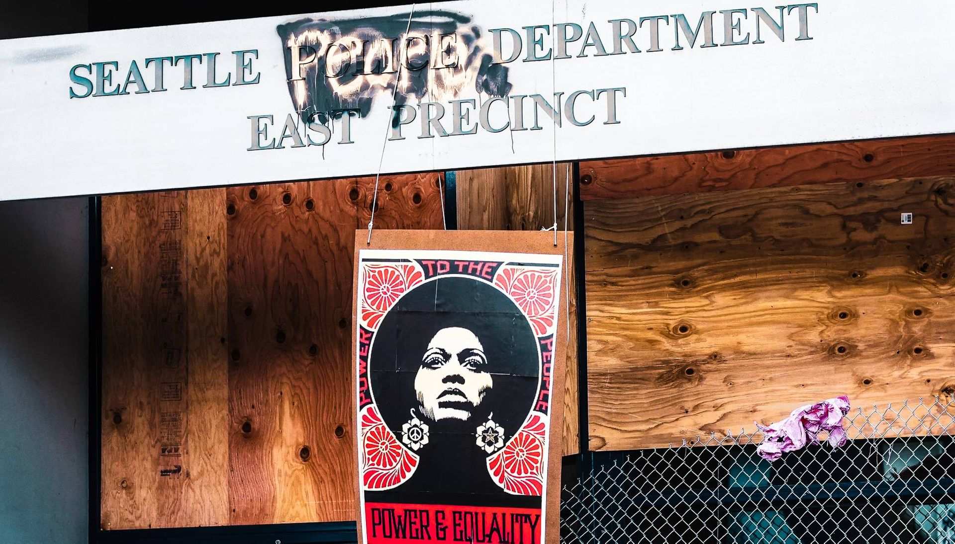 Seattle East Precinct Police Department sign defaced with Seattle People's Department and protest sign. Rewire PBS Our Future CHOP