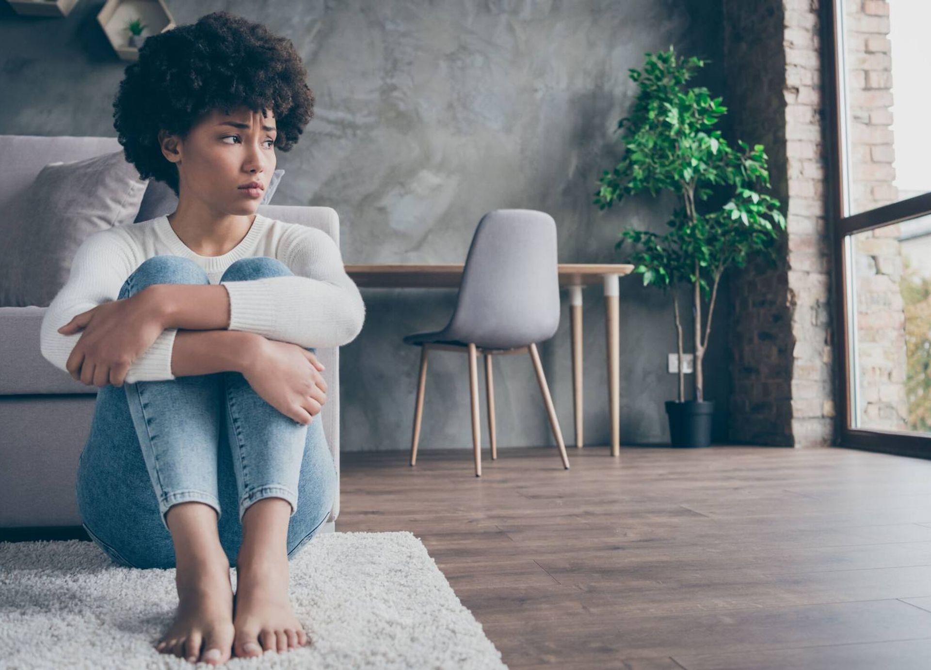 Woman sitting on floor looking out window