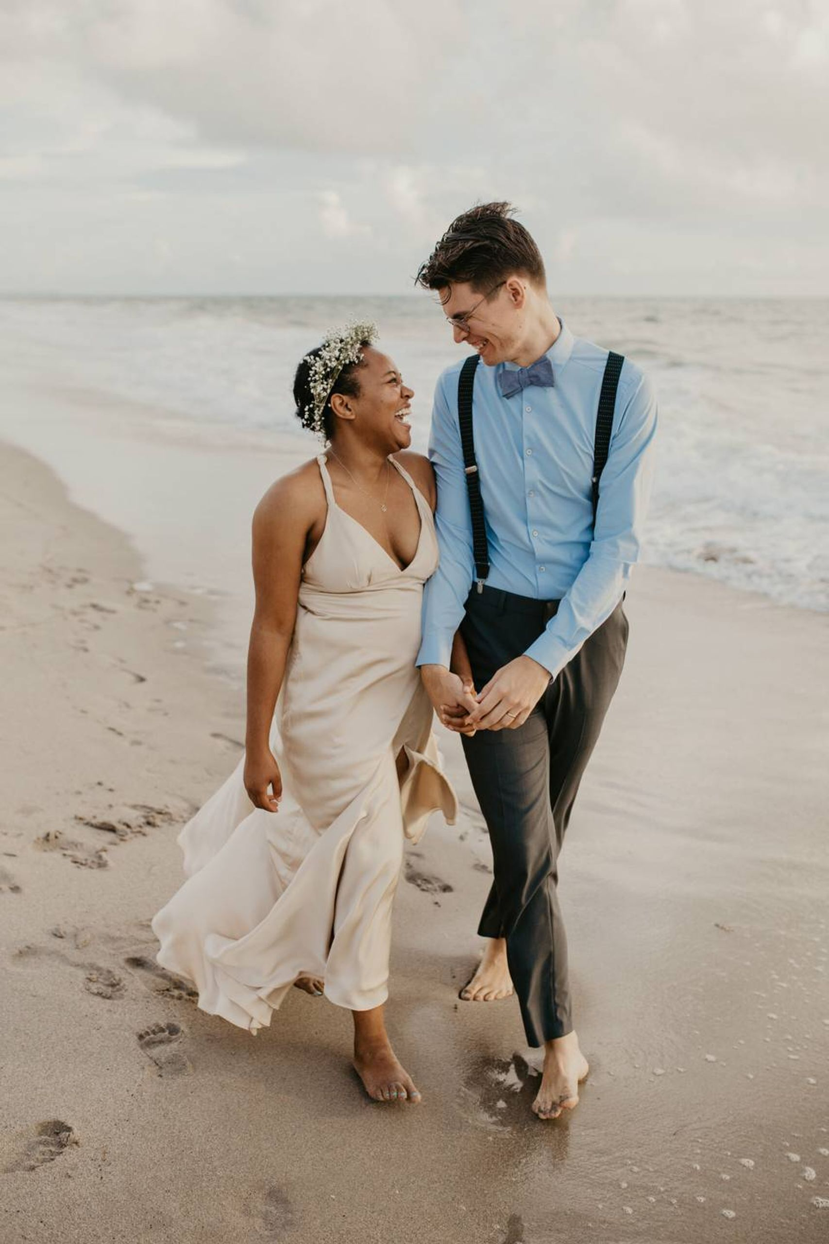 A young interracial couple walks on the beach, looking into each other's eyes and laughing. REWIRE PBS Our Future Love interracial couple