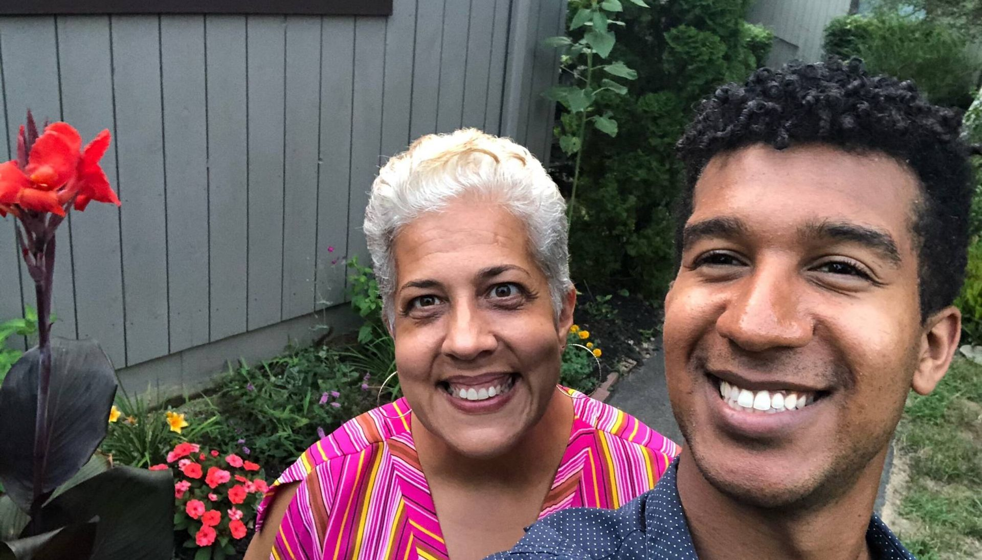 A son and his mom take a selfie outside in their garden in summer
