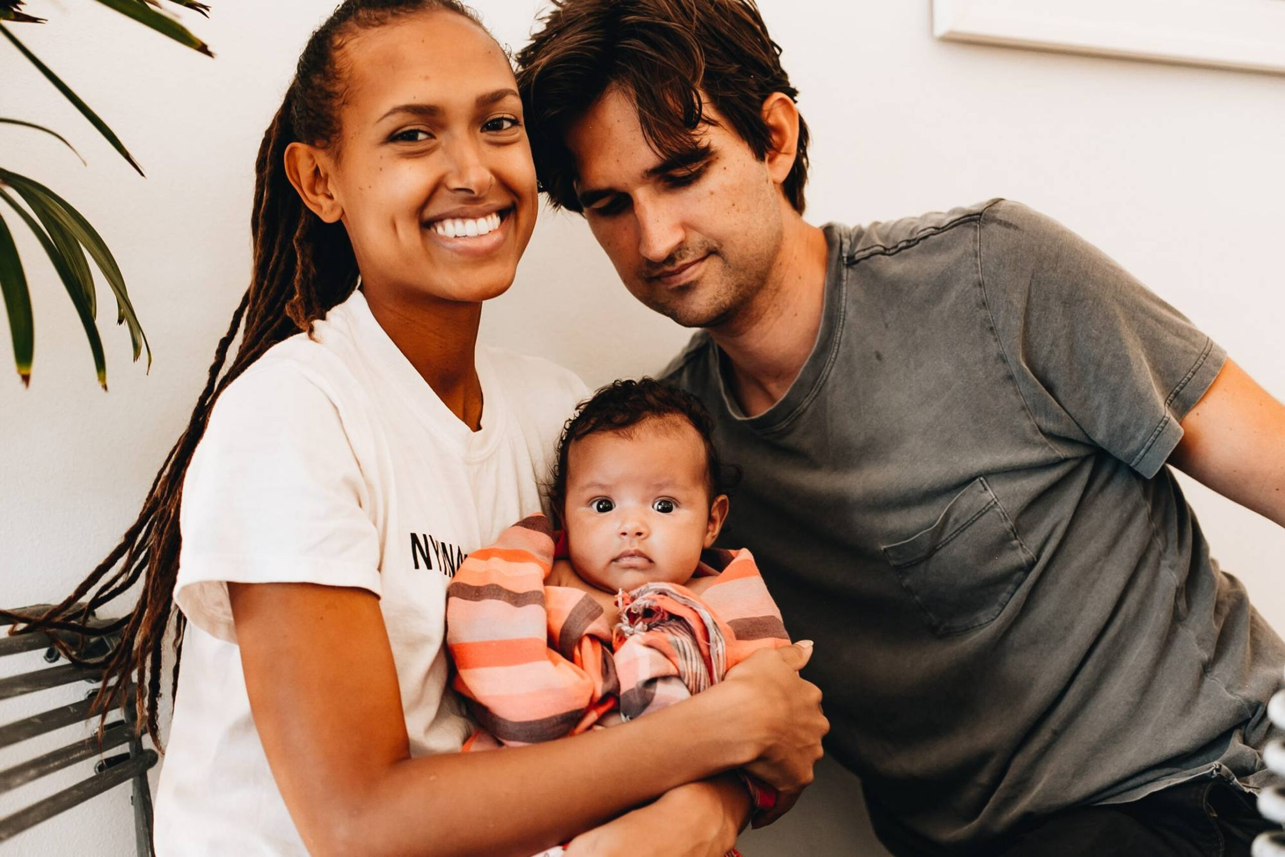 A young interracial couple holds a baby. REWIRE PBS Our Future Love interracial family