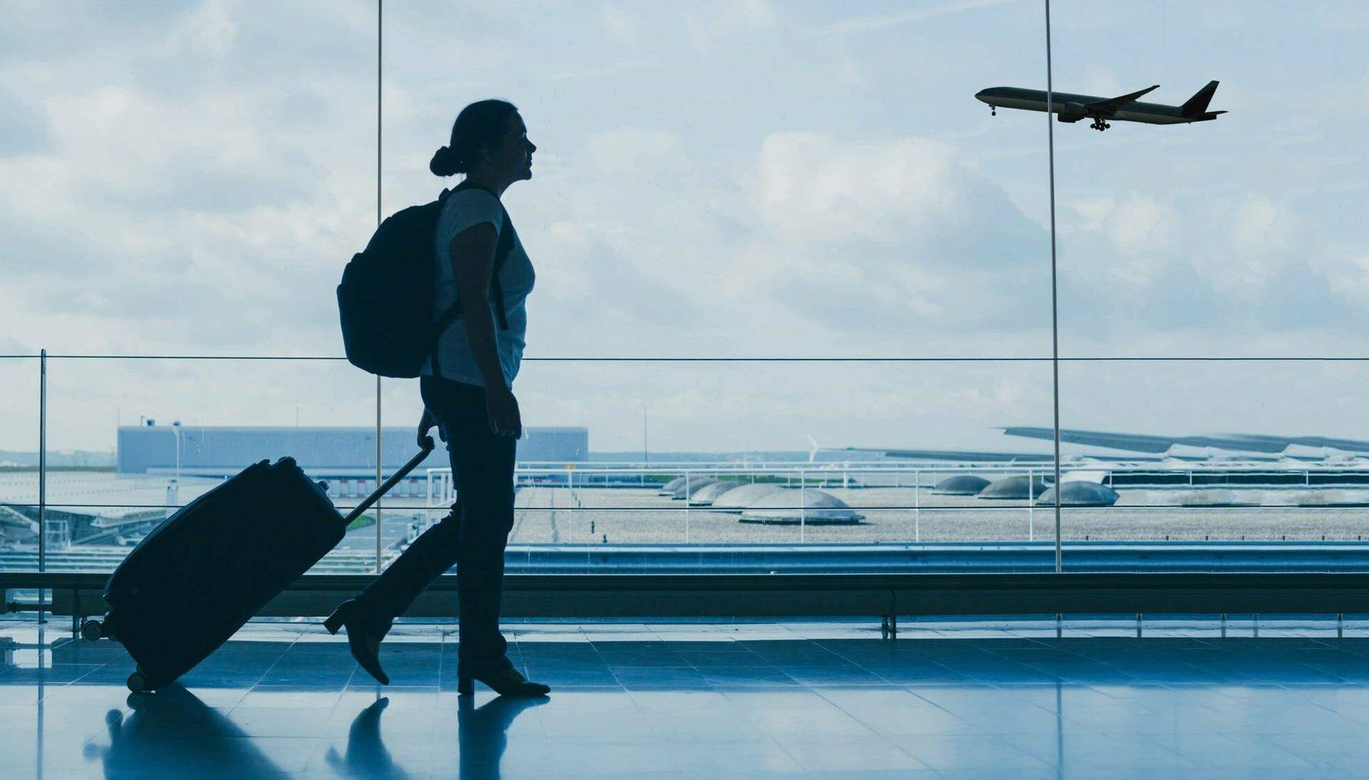Photo of a travel in silhouette walking in an airport carrying luggage while an airplane flies in the sky